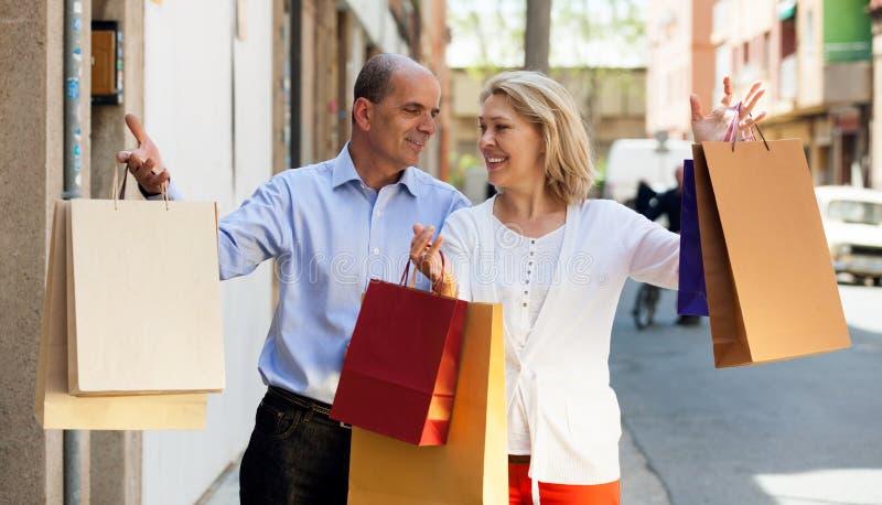 恋人在城市结合有购物游览和微笑 图库摄影