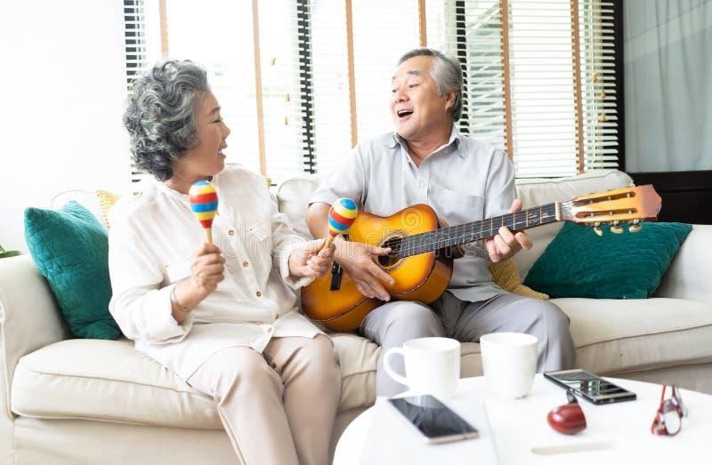 恋人在客厅 举行maracas的微笑的老人弹吉他的和她的妻子滑稽的画象跳舞和坐沙发 免版税库存图片