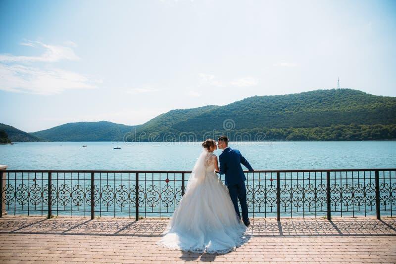 恋人在山和蓝色湖的背景亲吻 婚礼之日在一个惊人的美丽如画的地方 免版税库存照片