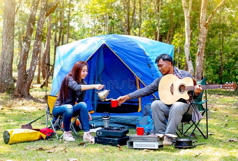 恋人夫妇在森林附近野营有与人戏剧吉他的放松的活动,并且妇女给他与一杯咖啡 免版税库存图片