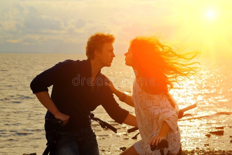 恋人夫妇坐在海岸的自行车在日落 免版税库存图片