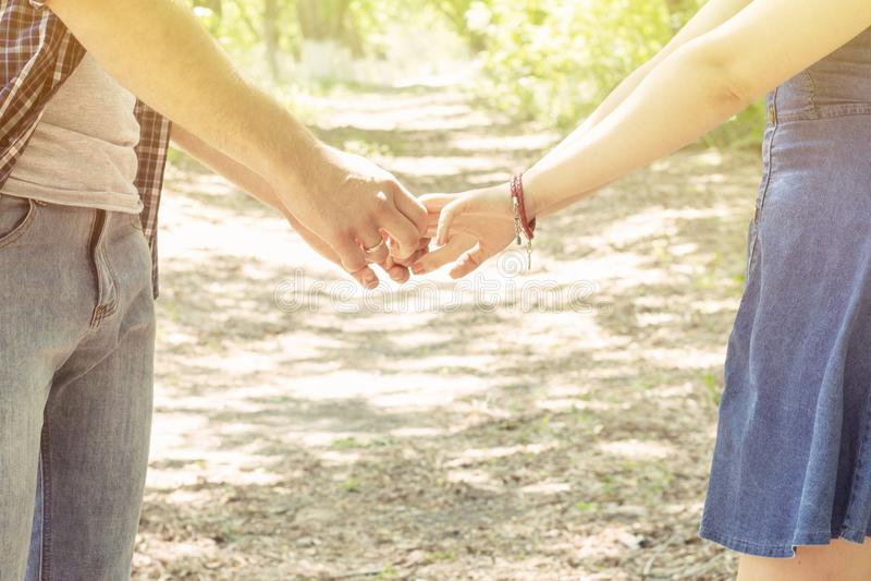 恋人握手 夫妇男孩和女孩立场晴朗的夏日 免版税库存图片