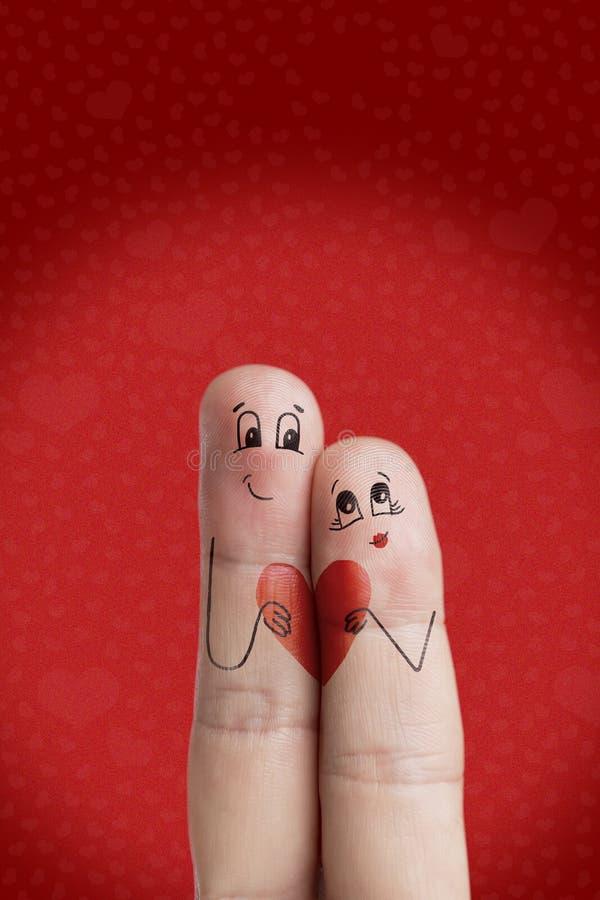 恋人是接受和拿着红色心脏 愉快的情人节题材系列 图象纵向股票妇女年轻人 免版税库存照片