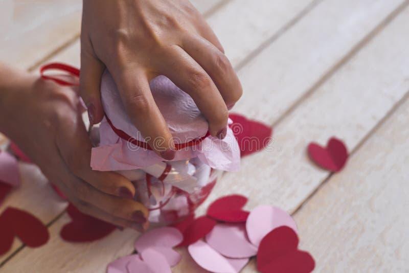 恋人` s天 手打开的玻璃瓶子或日期瓶子以欲望 在背景的红色纸心脏 图库摄影