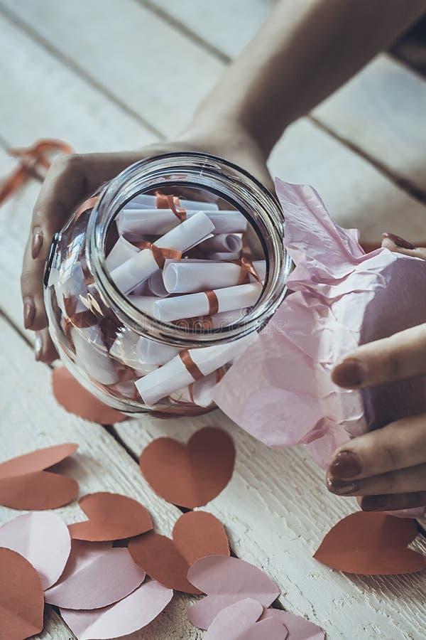 恋人` s天 手打开的玻璃瓶子或日期瓶子以欲望 在背景的红色纸心脏 库存图片