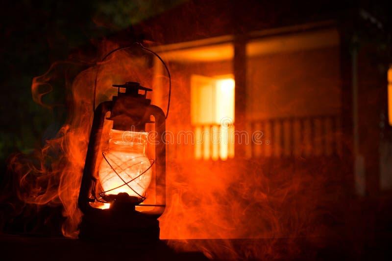 恐怖万圣夜概念 灼烧的老油灯在森林里在晚上 恶梦场面的夜风景 免版税库存照片