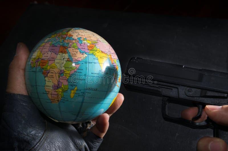 恐怖分子投入了枪对地球 免版税图库摄影