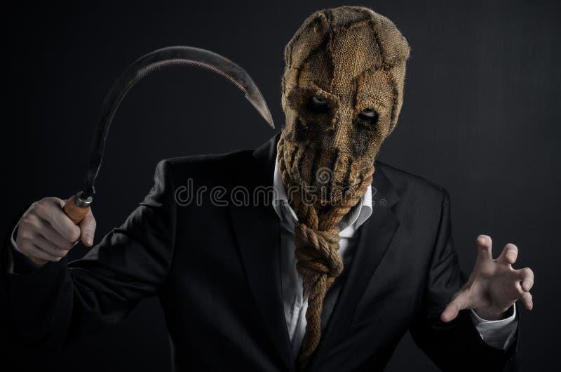 恐惧和万圣夜题材:在拿着镰刀的面具的一个残酷凶手老在黑暗的背景在演播室 库存照片