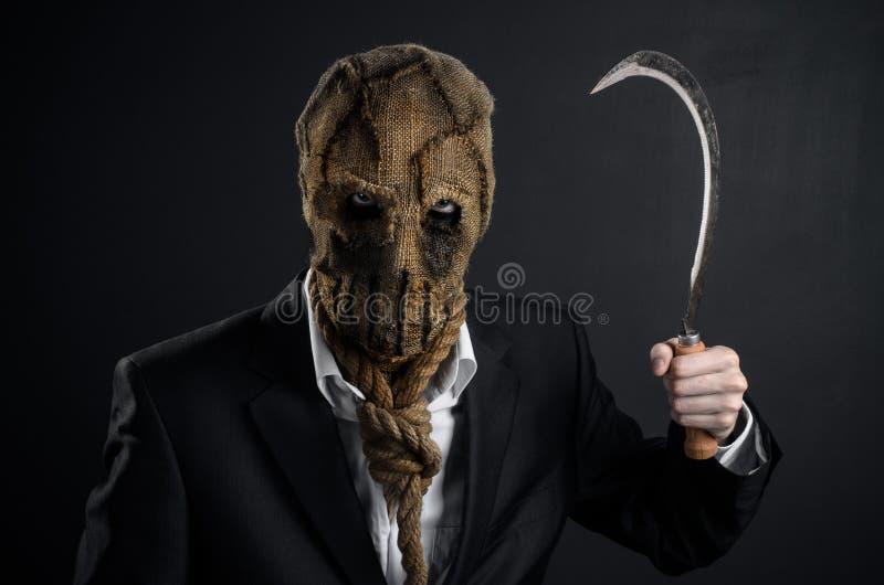 恐惧和万圣夜题材:在拿着镰刀的面具的一个残酷凶手老在黑暗的背景在演播室 库存图片