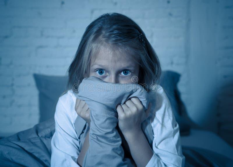 恐惧的失眠的逗人喜爱的女孩在掩藏在毯子后的晚上害怕黑暗和妖怪 免版税库存图片