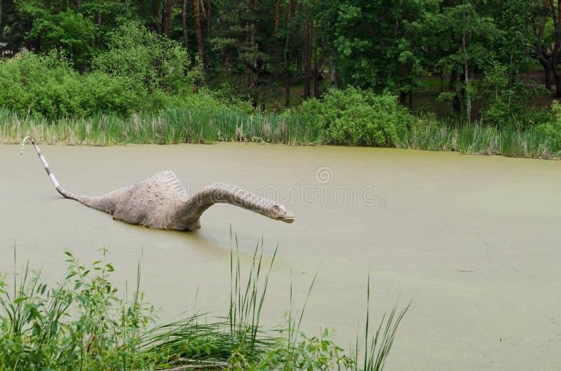 恐龙梁龙的模型在沼泽的 免版税库存图片