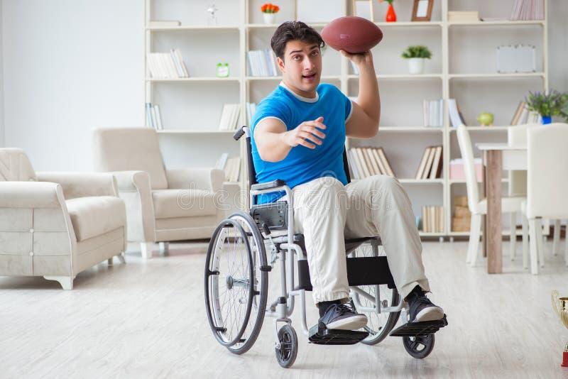 恢复在轮椅的年轻人美国橄榄球运动员 免版税库存图片