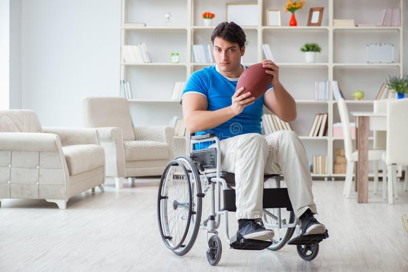 恢复在轮椅的年轻人美国橄榄球运动员 库存照片