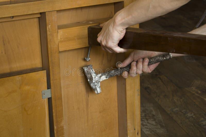 恢复有锤子的,特写镜头的木匠的手老家具 库存照片