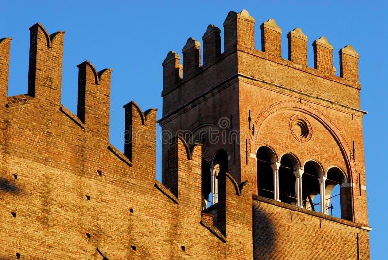 恩佐国王古老中世纪宫殿的墙壁和塔,照亮由太阳和有蓝天背景在波隆纳 免版税库存图片