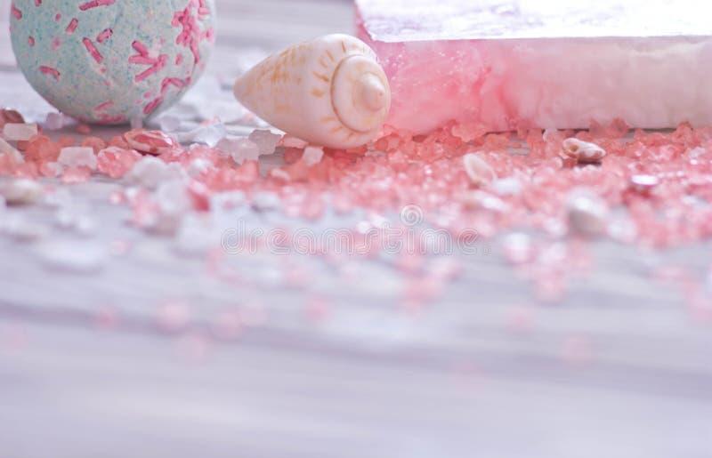 巴恩炸弹、贝壳、手工制造肥皂酒吧和桃红色温泉盐身体的关心 在前景的软的焦点 免版税库存照片