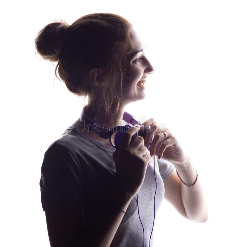 恳切地听到音乐,与耳机的少年笑的一个愉快的女孩的剪影在脖子,放松在白色的年轻女人 库存照片