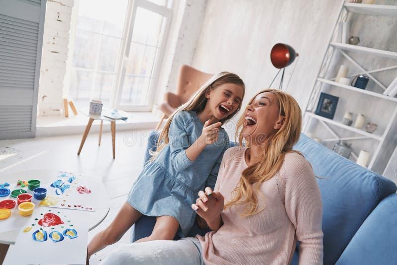 恳切的喜悦 笑的母亲和的女儿顶视图,当痛苦时 免版税库存照片