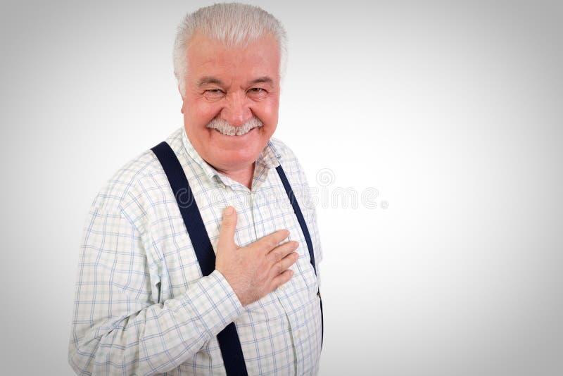 恳切的老人用他的在他的心脏的手 免版税库存照片
