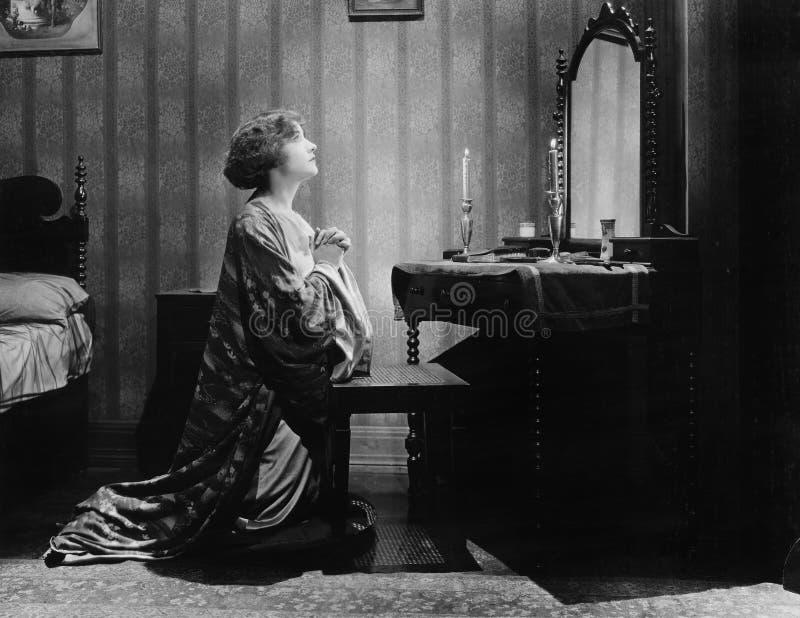恳求在一个镜子前面的一个少妇的档案在她的床室(所有人被描述不是更长生存和没有庄园 免版税图库摄影