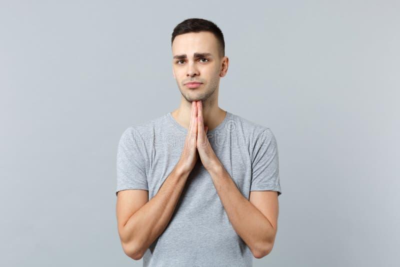 恳求的年轻人画象看照相机的便服的,折叠了他的手,在灰色墙壁上隔绝的祈祷 库存图片