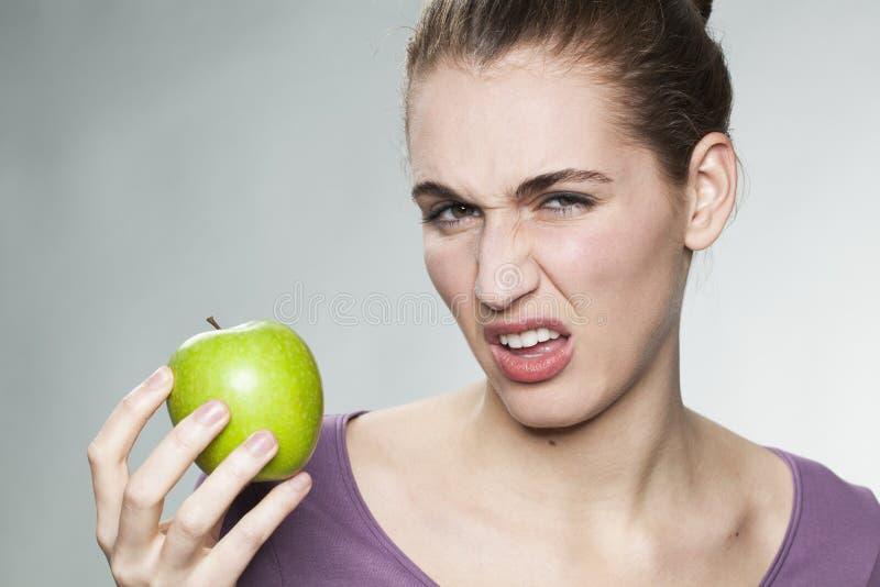 恶心的妇女怏怏不乐对于她的苹果 免版税图库摄影