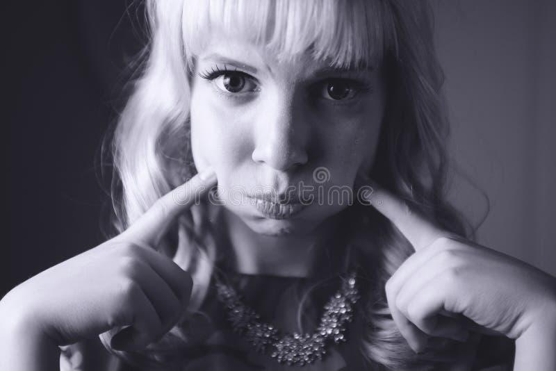恶心的少妇吹的面颊画象  黑色白色 库存图片