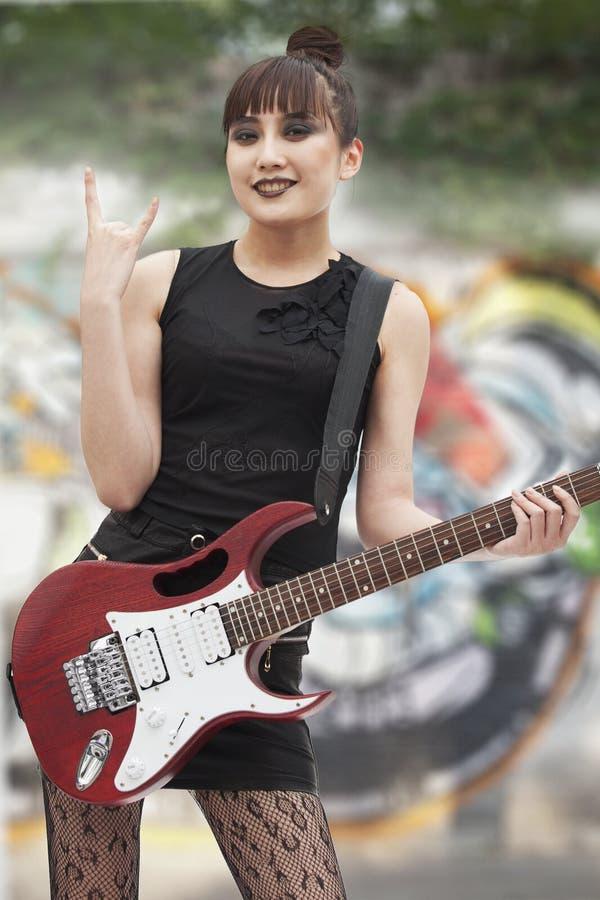 给恶魔垫铁用她的手和拿着吉他的年轻庞克摇滚乐女孩 库存照片