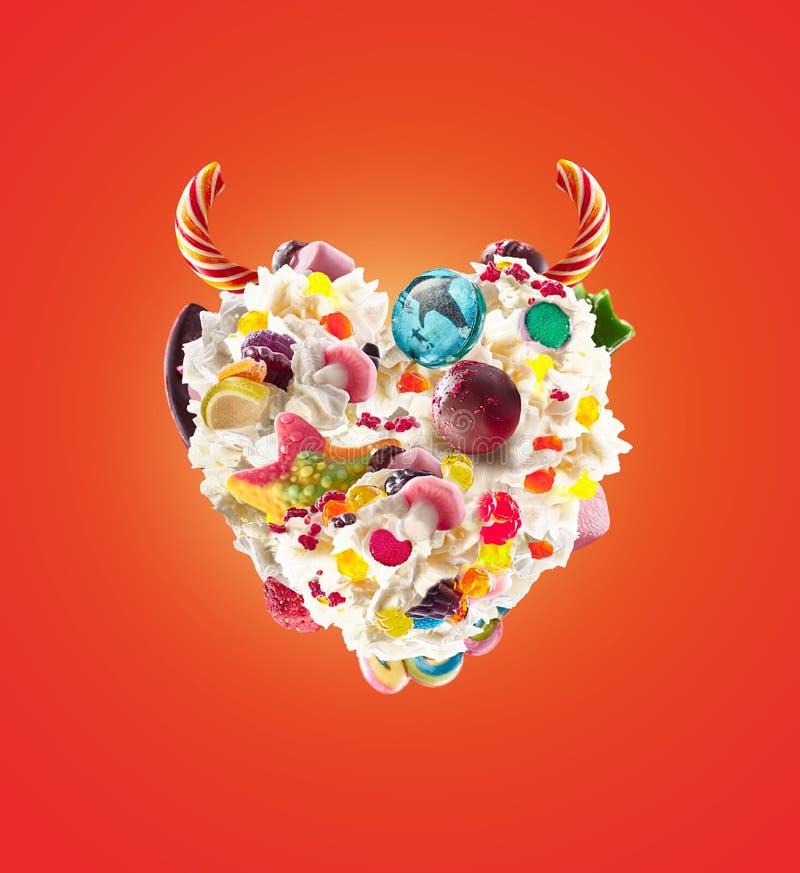 恶魔心脏与甜点和打好的奶油,正面图的奶昔 与被鞭打的奶油和恶魔垫铁的甜概念 免版税库存图片