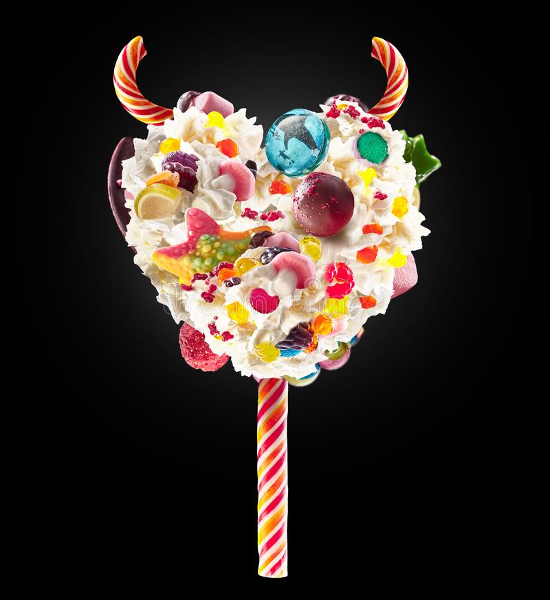 恶魔心脏与甜点和打好的奶油,正面图的奶昔lolipop 与打好的奶油的甜恶魔lolipop概念 免版税库存图片