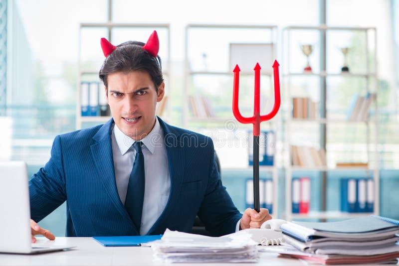 恶魔恼怒的商人在办公室 免版税库存图片