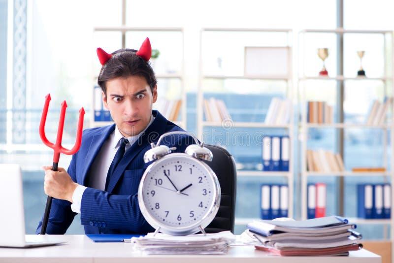 恶魔恼怒的商人在办公室 库存照片