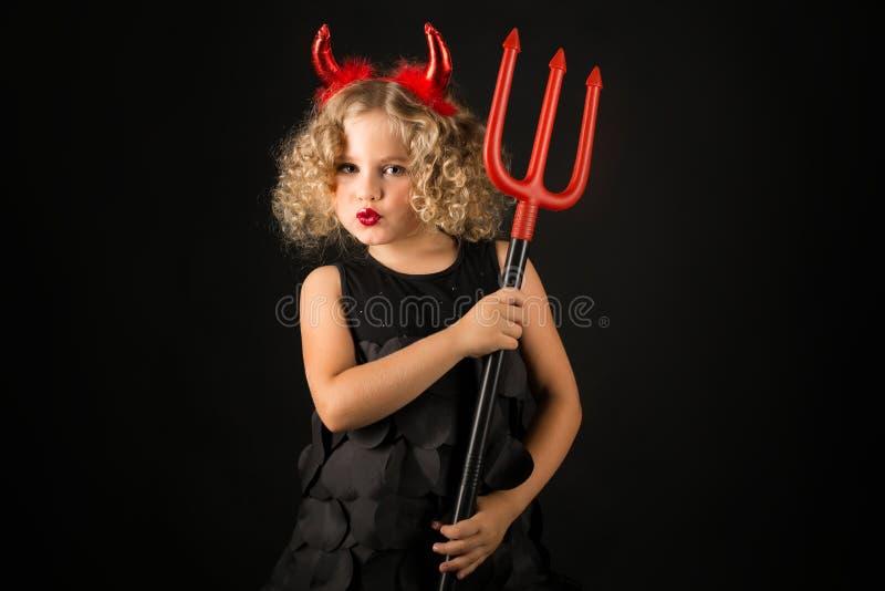 恶魔服装的逗人喜爱的女孩 免版税图库摄影