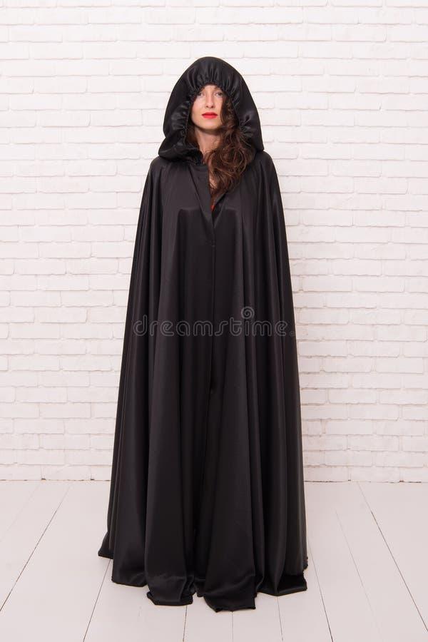恶魔概念 万圣节化妆舞会 o 俏丽的妇女恶魔 在黑斗篷标志的死亡 吸血鬼 库存图片