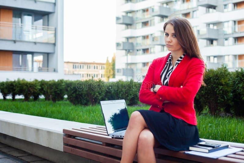 年轻恼怒专业女商人坐室外与胳膊 免版税库存图片