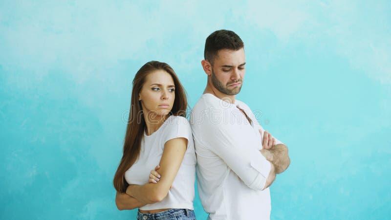 恼怒年轻的夫妇生气和站立后方在蓝色背景 免版税库存照片