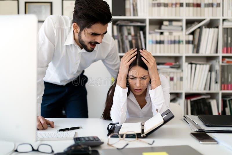 恼怒的上司叫喊对他的雇员在办公室 免版税库存图片