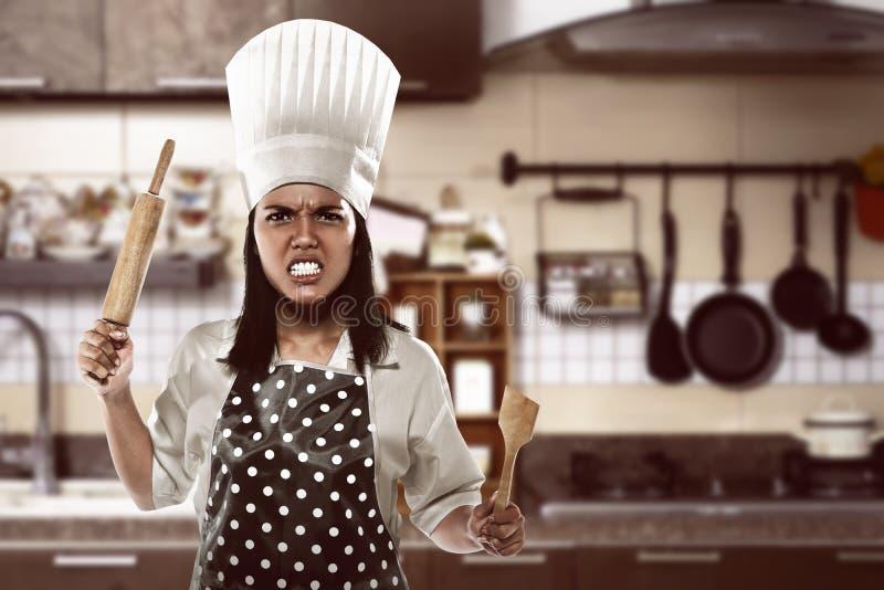 恼怒的亚裔妇女厨师 库存图片
