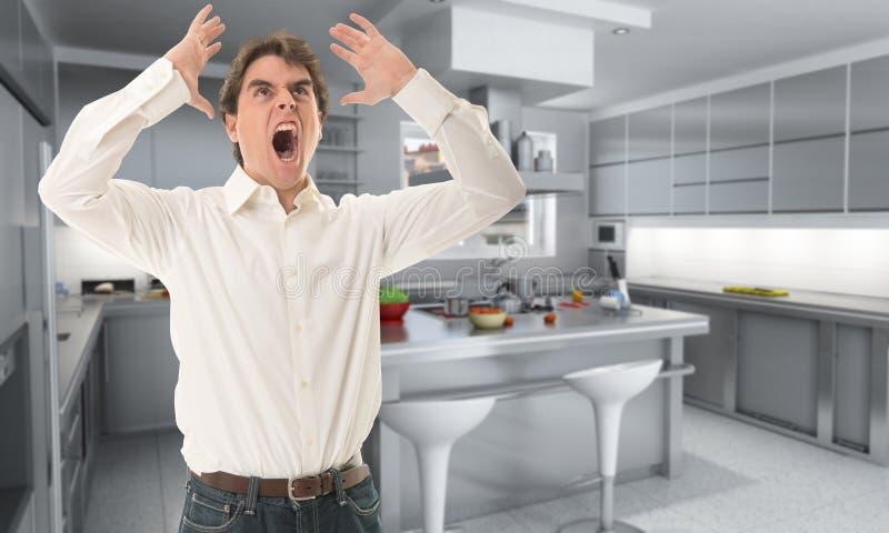 恼怒的人在厨房里 库存照片