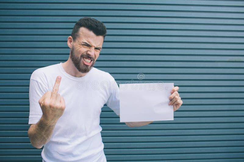 恼怒的人是站立和摆在照相机 他显示无名指 它是坏标志 并且人拿着空白的片断 免版税库存照片