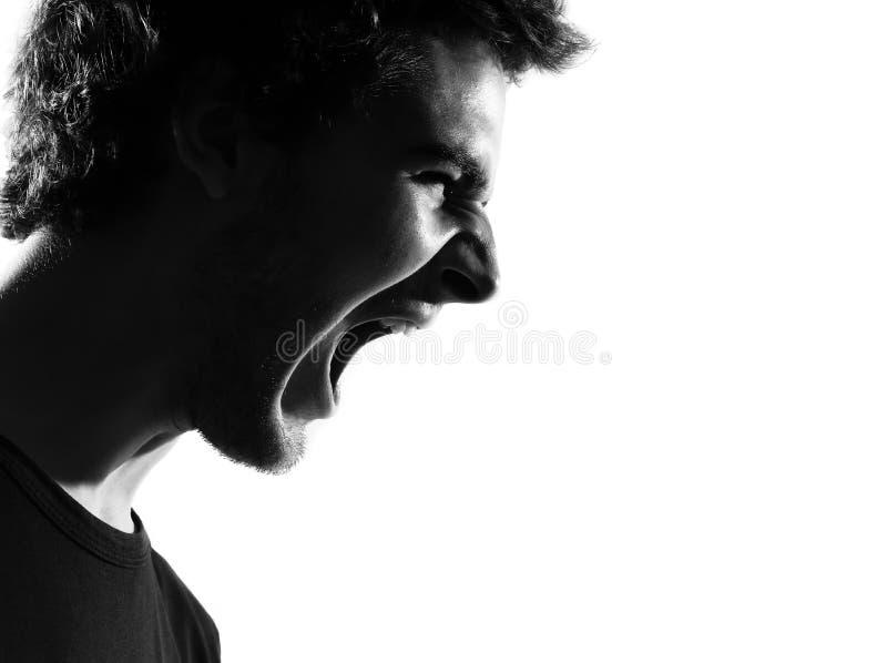 恼怒的人纵向叫喊的剪影年轻人 库存照片