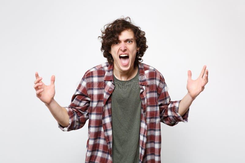 恼怒的叫喊的年轻人画象看照相机,传播的手的便服的隔绝在白色墙壁上 免版税库存图片
