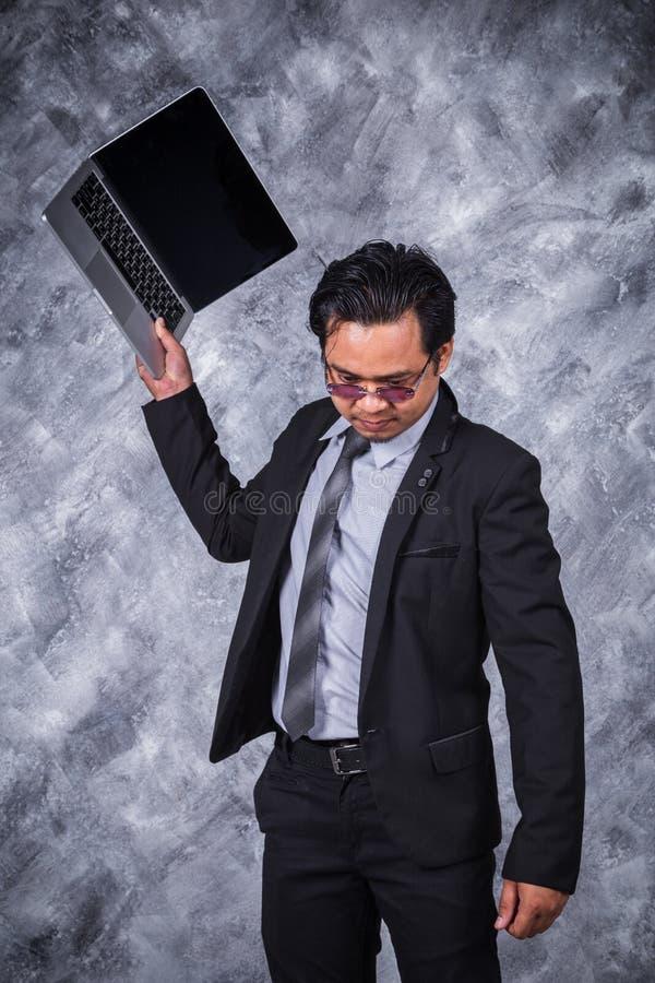 恼怒的商人丢掉他的膝上型计算机 库存图片