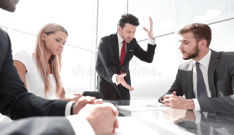 恼怒的商人在与企业队的一次工作会上 免版税库存照片