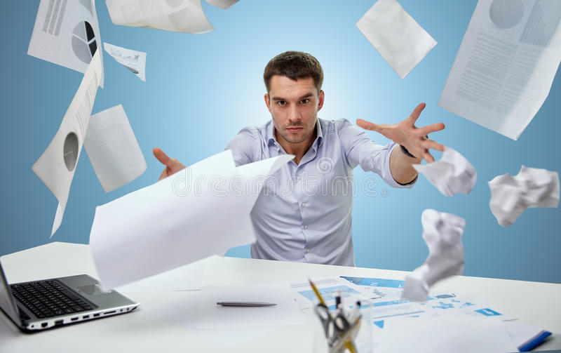 恼怒的商人投掷的纸在办公室 免版税库存图片
