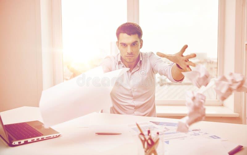 恼怒的商人投掷的纸在办公室 图库摄影