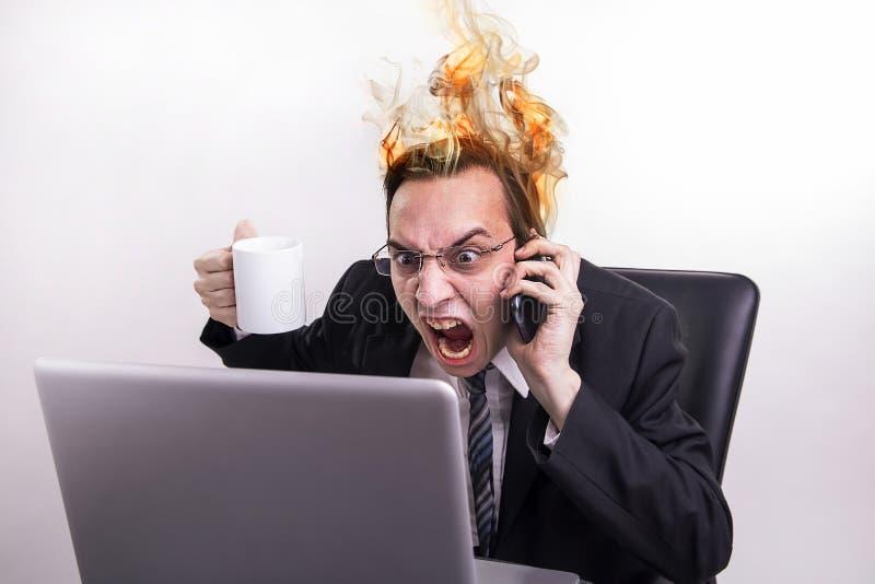恼怒的商人谈话在手机和尖叫在他的膝上型计算机在办公室,而他的头烧 免版税库存照片