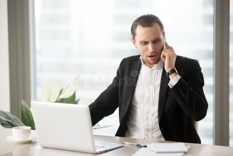 恼怒的商人谈话在手机 免版税库存照片