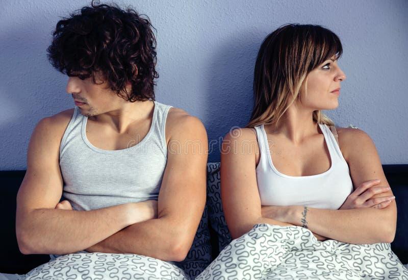 恼怒的夫妇坐床用横渡的手 库存图片