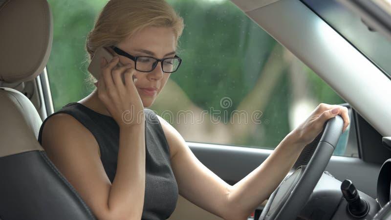 恼怒的女商人争吵与智能手机的丈夫在汽车,重音 库存图片